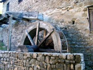 Un primo piano della ruota idraulica: si distinguono i cassetti e la parte finale della roggia, chiamata doccia.