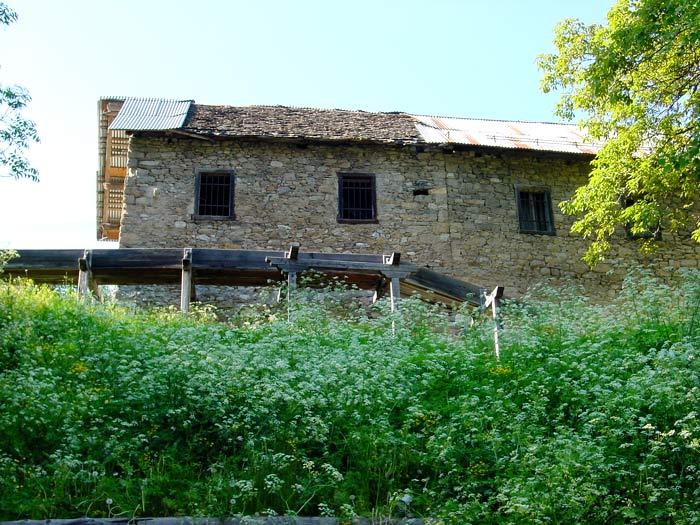 La facciata sud del mulino Calligaro con un tratto della roggia.